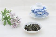 Feuilles de thé avec la tasse de thé et les fleurs photo libre de droits