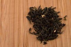 Feuilles de thé de vert de feuilles mobiles sur le bois Images stock