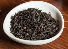 Feuilles de thé noires dans la cuvette blanche sur le fond en bois Image stock