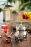 Feuilles de thé sèches sur la cuillère et la théière Image libre de droits