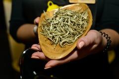 Feuilles de thé sur une lame en bois Image stock