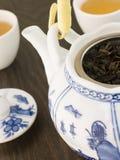 Feuilles de thé vertes dans un bac de thé avec des cuvettes Photographie stock libre de droits