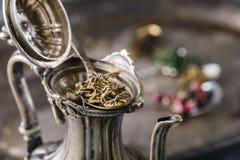 Feuilles de thé vertes sèches dans la cuillère de vintage en métal Images libres de droits