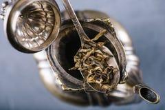 Feuilles de thé vertes sèches dans la cuillère de vintage en métal au-dessus de la théière ouverte Photos stock