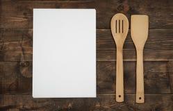Feuilles de vaisselle de cuisine en bois et de papier blanc pour des recettes Photos libres de droits