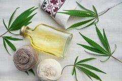 Feuilles des cannabis, boules de fil et bouteille avec de l'huile sur la toile photo stock