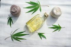 Feuilles des cannabis, boules de fil et bouteille d'huile de chanvre sur le canv Photos stock
