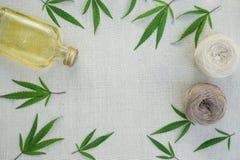 Feuilles des cannabis, boules de fil et bouteille d'huile de chanvre sur le canv Images libres de droits
