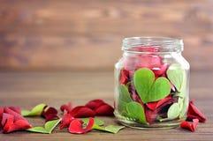 Feuilles et pétales de rose en forme de coeur dans le pot Photographie stock