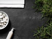 Feuilles et serviette de bambou avec de la crème sur un fond d'ardoise Image stock