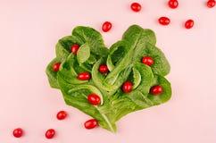 Feuilles fraîches de salade et tomates-cerises rouges comme coeur sur le fond rose Nourriture suivante un régime saine de ressort Photographie stock
