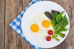 Feuilles fraîches de salade de petit déjeuner et deux oeufs au plat Photos libres de droits