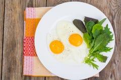 Feuilles fraîches de salade de petit déjeuner et deux oeufs au plat Photo libre de droits