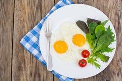 Feuilles fraîches de salade de petit déjeuner et deux oeufs au plat Photographie stock