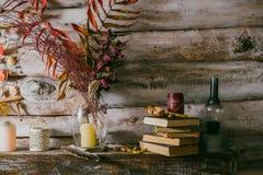 Feuilles sèches dans un vase Intérieur de cru La de livres, de bougie et d'oli images libres de droits