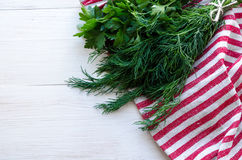 Feuilles vertes de persil et d'aneth sur la serviette de toile naturelle sur le fond en bois Images stock