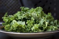 Feuilles vertes fraîches de chou vert sur la table noire, nourriture végétarienne saine photographie stock libre de droits