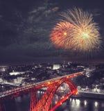 Feux d'artifice au-dessus de pont rouge sur un fond monochromatique Image stock
