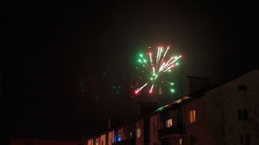 Feux d'artifice dans le ciel nocturne au-dessus des maisons Photographie stock