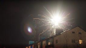 Feux d'artifice dans le ciel nocturne au-dessus des maisons Photo libre de droits