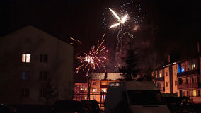 Feux d'artifice dans le ciel nocturne au-dessus des maisons Image libre de droits