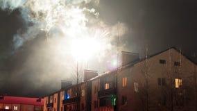 Feux d'artifice dans le ciel nocturne au-dessus des maisons Images stock