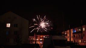 Feux d'artifice dans le ciel nocturne au-dessus des maisons Photographie stock libre de droits