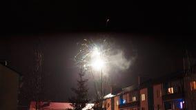 Feux d'artifice dans le ciel nocturne au-dessus des maisons Image stock