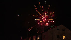 Feux d'artifice dans le ciel nocturne au-dessus des maisons Photos libres de droits