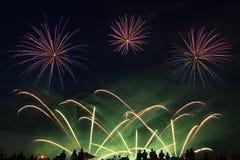 Feux d'artifice dans le ciel nocturne et les silhouettes des personnes de regard Image stock