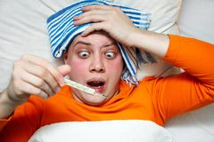 Fever. Portrait of a sick man lying in bed with fever Stock Photo