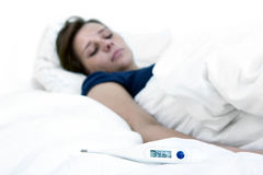 Fever. Thermometer, indicating high fever, lying on a bed, with a sick woman in the background royalty free stock images