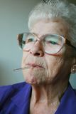 Fever. Senior with thermometer in her mouth Royalty Free Stock Photo