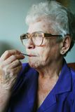 Fever. Close up of a senior woman with thermometer in her mouth Royalty Free Stock Photos