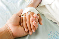 Fever patients. Mother holding child's hand who fever patients have IV tube Royalty Free Stock Images
