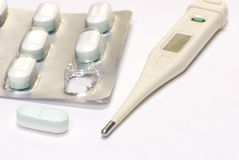Fever and and pill. Thermometer and pill blisterpack ready to get rid of that fever Royalty Free Stock Image