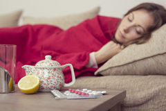 Fever. Sick woman covered with a blanket lying in bed with high fever and a flu, resting. Teapot, pills and lemon on the table, focus on the teapot stock photo