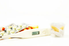 Fever. Thermometer with elevated temperature and various pills Royalty Free Stock Photography