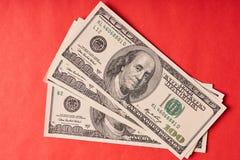 Few Amerykańscy dolary na papierowym czerwonym tle obrazy royalty free