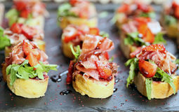 A few appetizing bruschettes from white bread with bacon, brown Stock Image