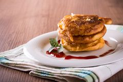 Few apples in dough with jam on white plate and cloth. Horizontal photo of few cinnamon apples coated in pancake dough. Sweet food placed on white plate with Royalty Free Stock Images