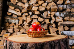 A few  apples on the stump in the background of birch firewood. A few  apples and basket on the stump in the background of birch firewood Stock Photography
