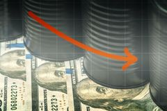 Few barrels of oil on dollars and a red down arrow - lower oil prices concept.  royalty free stock image