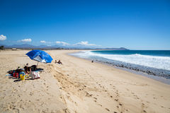 FEw beach chair in a blue sky day in the beach of Puerto Escondida in Mexico. Royalty Free Stock Photo