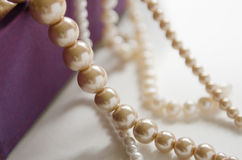 few beads of pearls hanging on a purple gift box Royalty Free Stock Image