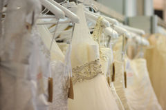 A few beautiful wedding dresses. Hanging on the stand Stock Photo