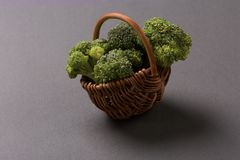 Few broccoli branches in wooden basket on gray background. Side view Royalty Free Stock Images