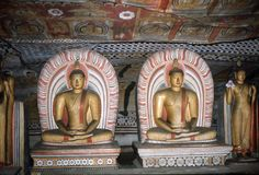 1977. Sri Lanka. Buddhas, in Dambulla Cave Temple. A few Buddha figures amongst many in one of the five caves Stock Photo