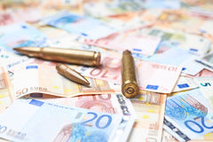 Few bullets over the pile of money Royalty Free Stock Images