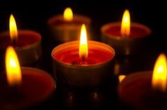 A few burning candles in the dark. On a beautiful black background close-up royalty free stock photography